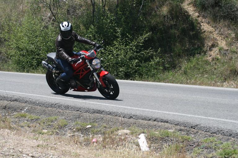 Motorkár jazdí po ceste, červeno-čierna motorka