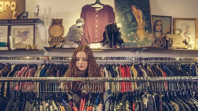 Žena si prezerá tovar v obchode s oblečením