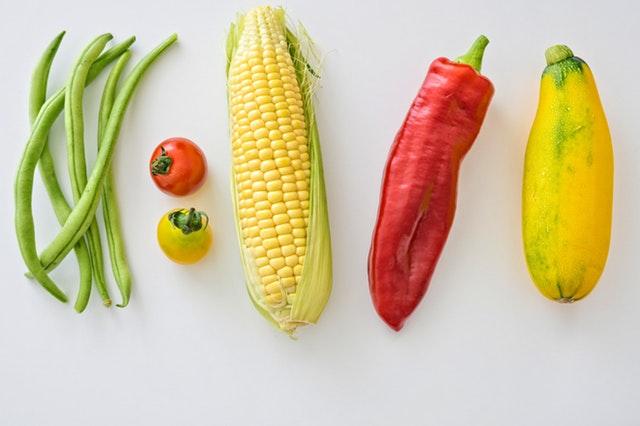 Fazuľové lusky, paprika, paradajky, kukurica a cuketa na bielom pozadí