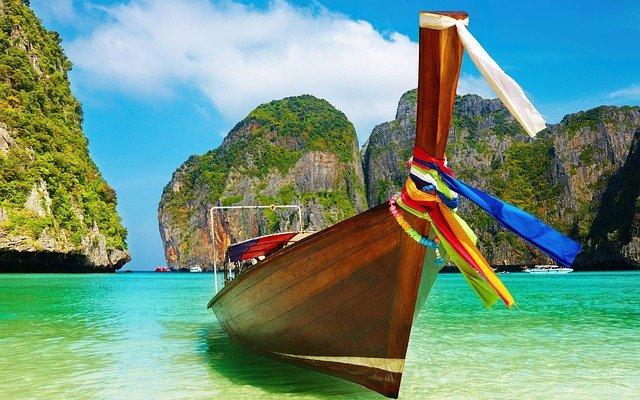 Malá drevená loďka stojí na pieskovej pláži v zátoke.jpg