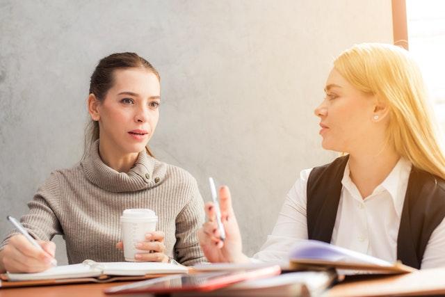 Dve ženy sedia pri stole a diskutujú.jpg