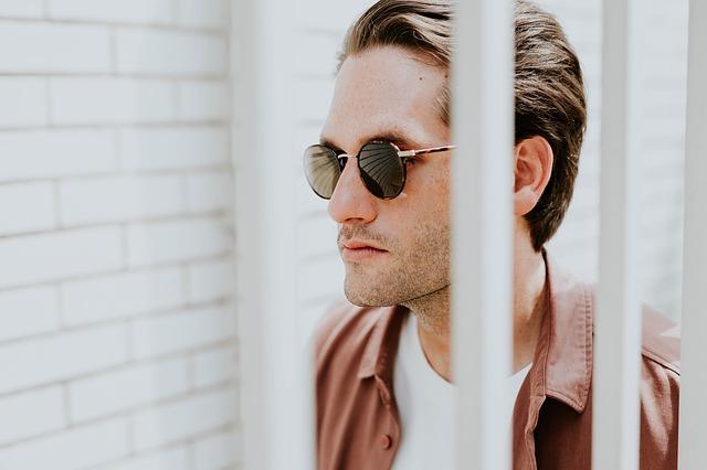 Muž v slnečných okuliaroch za bielymi mrežami.jpg