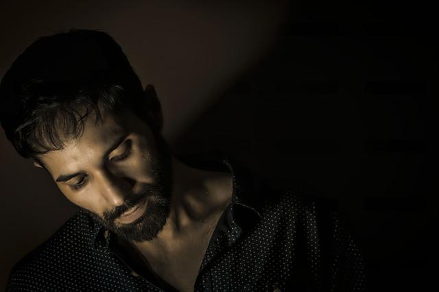 Muž s tmavými vlasmi, v čiernej košeli s bodkami v tme.jpg